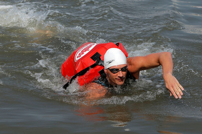 World champion swimmer, Ryan Lochte, swims the Hudson River with a waterproof pack full of Pizzeria Pretzel COMBOS(R) baked snacks to make the most epic pizza delivery ever to expectant fans at the Midtown Ferry Terminal in New York City. Fans gathered to greet Lochte following his swim-delivery, which was in effort to launch a call-to-action encouraging fans everywhere to share their own epic idea for eating new 7 Layer Dip Tortilla COMBOS(R) baked snacks at Facebook.com/COMBOS.  (PRNewsFoto/Mars Chocolate North America)