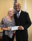 Andrew Haskins of the Altic-Orlovic Agency Office of American Income Life presents $5,000 to Linda Krieg, acting CEO of the Center for Missing and Exploited Children