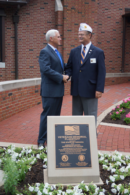 Indianapolis -- Indiana Governor Mike Pence and Indiana Department of The American Legion's Commander Ed Trice shake hands outside of the official Governor's Residence Wednesday, June 4, 2014 after jointly dedicating a marker stone and flagpole in honor of Indiana's veterans. (PRNewsFoto/American Legion Department of..)