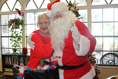 Long time Manor Oaks resident 90 year old Agnes Ballard poses with Santa (aka Maintenance Director Michael Homer) after receiving her gift.  (PRNewsFoto/Marrinson Senior Care Residences)