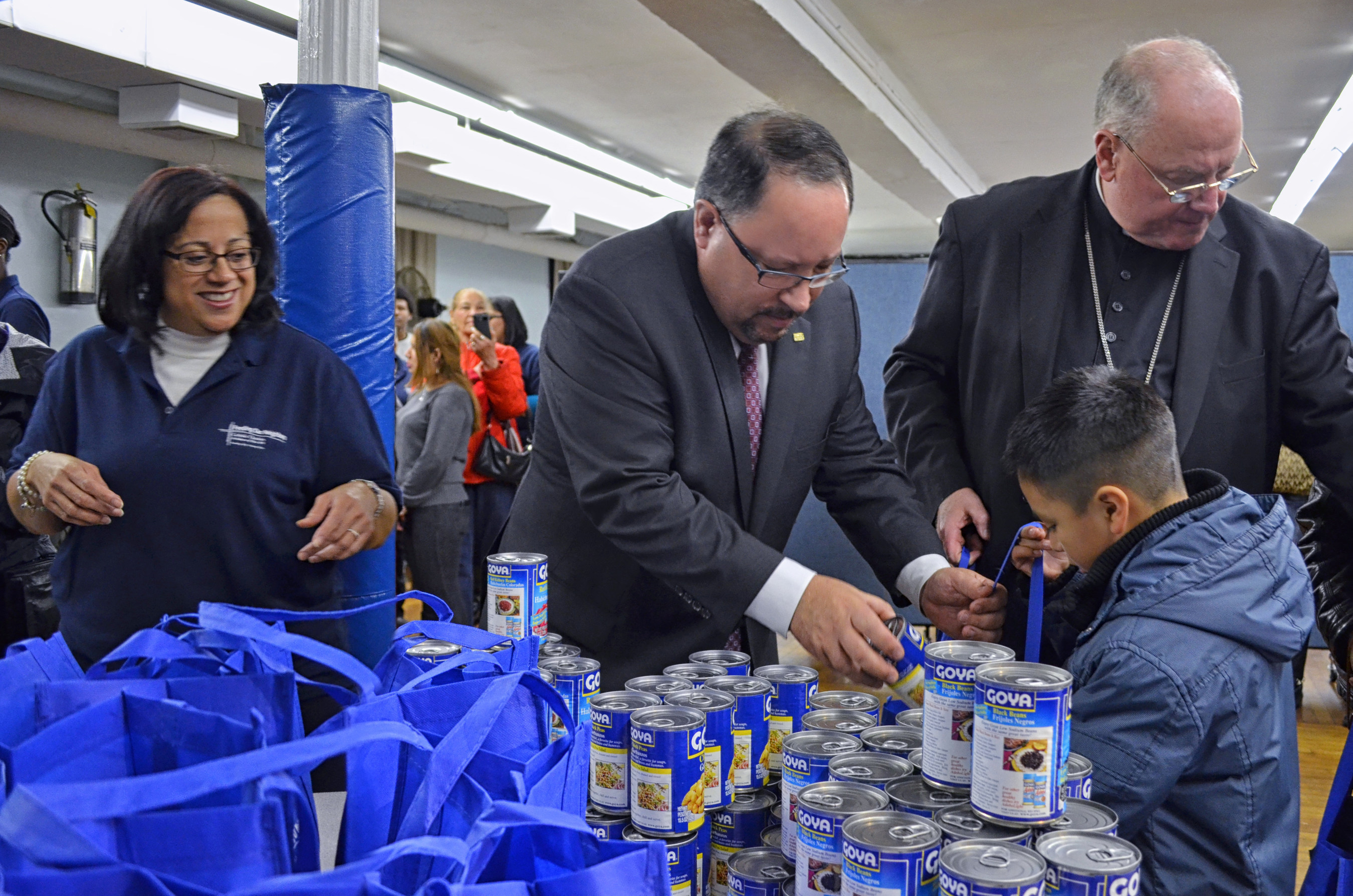President Bob Unanue of Goya Foods, Cardinal Dolan and Catholic Charities of NY help pack 300,000 pounds of ...