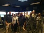 Lt. Col. John Lockett, Dickey's Associate Director of Franchise Relations Aaron Brewer and Dickey's Founder Roland Dickey, Sr. pose with airmen at Keesler Air Force Base.