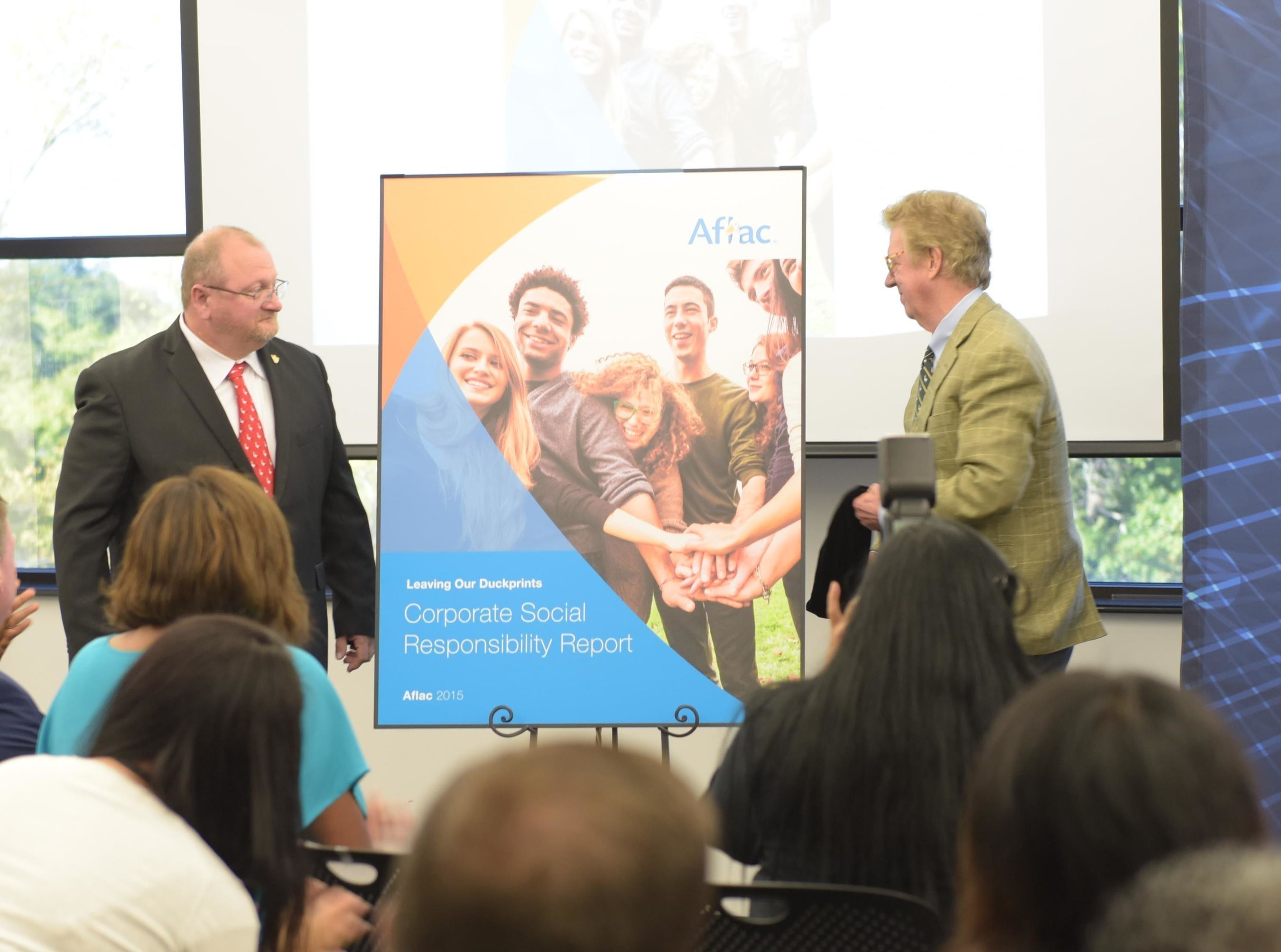 Aflac Chairman and CEO Dan Amos (r.) and 2015 Hero of the Fortune 500 Award winner James Mailman unveil Aflac's 2015 Corporate Social Responsibility Report at a company celebration in Columbus, Georgia. See the report at Aflac.com/csrreport
