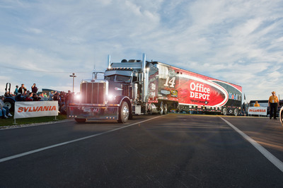 "Kicking off the SYLVANIA 300 race weekend, NASCAR Sprint Cup Series haulers arrived at New Hampshire Motor Speedway with headlights beaming as part of the ""Hauler Headlights for Safer Nights"" initiative during the speedway's FanFest celebration. SYLVANIA Automotive Lighting started the program in 2010 to promote nighttime driving safety and headlight maintenance.  (PRNewsFoto/OSRAM SYLVANIA)"