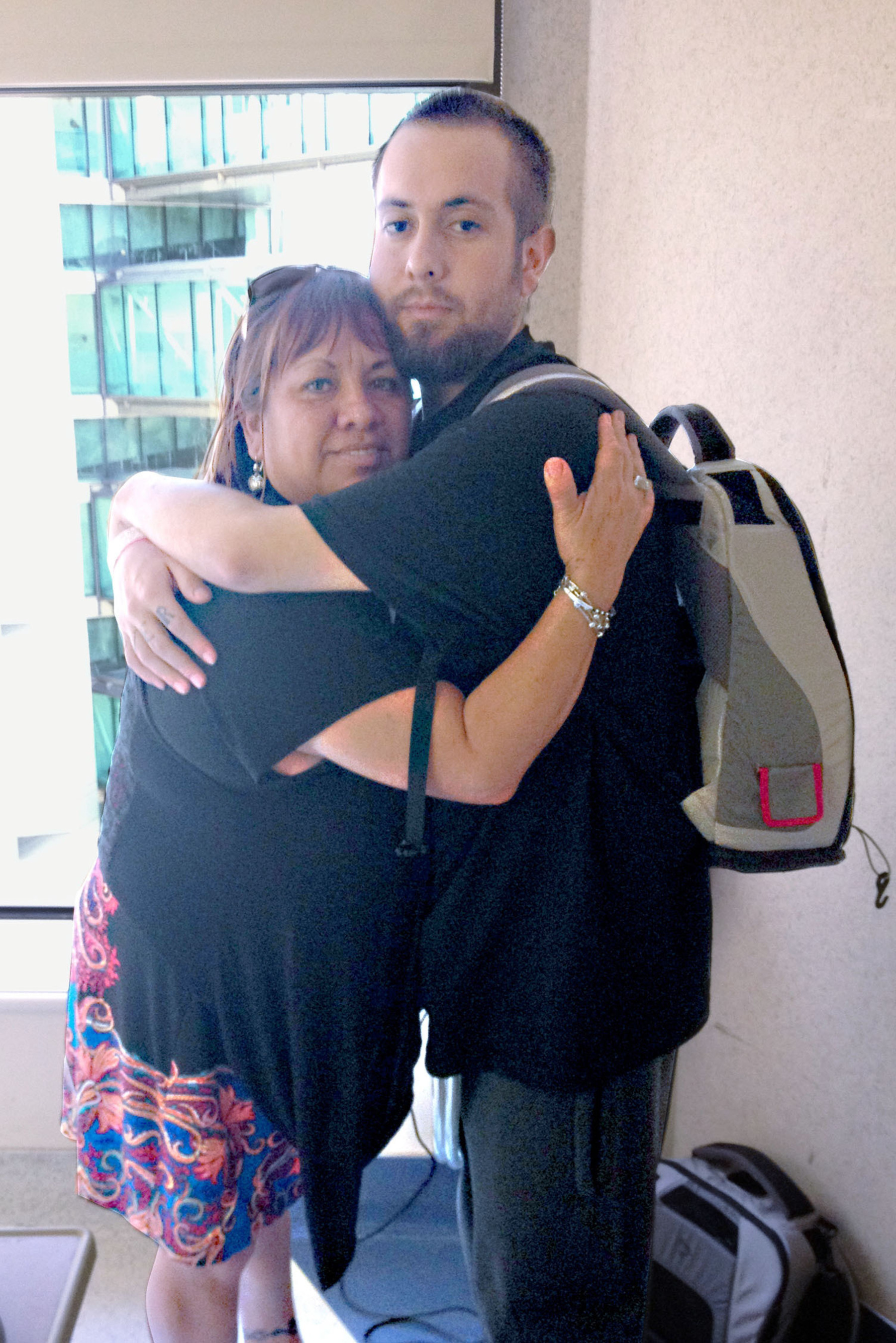 Kevin Stroh's mom, Esperanza Longo, feared for her son when he was diagnosed with the same disease that took her husband's life, congestive heart failure. Kevin is wearing his 13.5 pound Freedom portable driver in the backpack that powers the SynCardia Total Artificial Heart. Use of the SynCardia Total Artificial Heart provided Kevin with a bridge to human heart transplant and a much happier outcome.  (PRNewsFoto/SynCardia Systems, Inc.)