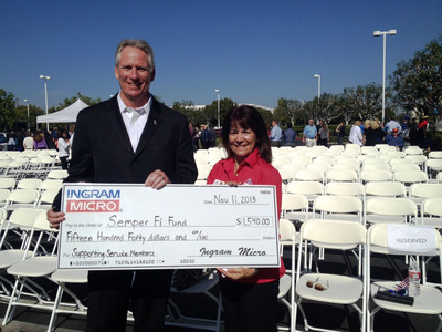 Robert Gifford, executive vice president, Ingram Micro Logistics, presents a check for $1,540 to Ester Rilea, Community Outreach Representative for the Semper Fi Fund. The donation for the entire amount was collected by and from the generous donations of Ingram Micro associates at their Santa Ana, Calif. office.  (PRNewsFoto/Ingram Micro Inc.)