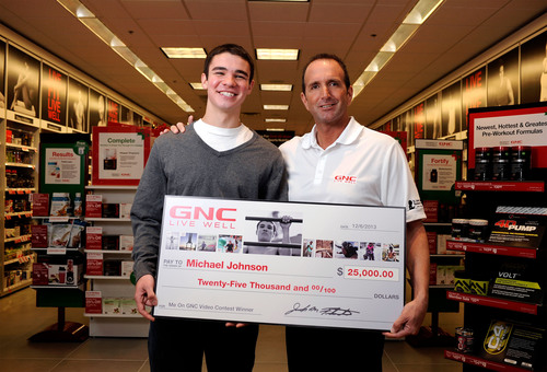 'ME ON GNC' Video Contest winner Michael Johnson and Patrick McKewon, District Sales Director for GNC. (PRNewsFoto/GNC Holdings, Inc.)