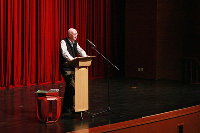 Irish poet, Peter Fallon, is reading his poem to the audience at Beijing's Keystone Academy.