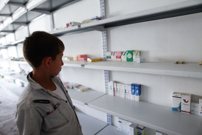 A young Syrian boy surveys the almost-empty shelves in his father's pharmacy in Syria. Sam Tarling/Save The Children.  (PRNewsFoto/Save the Children)