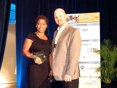 Kimberly Jackson, Sr. Manager of Enterprise Mobility & Wireless Solutions of American Airlines, accepting the 2012 Mobilizer Award with Ron Wilson, Director, North American Sales of SOTI Inc.  (PRNewsFoto/SOTI Inc.)