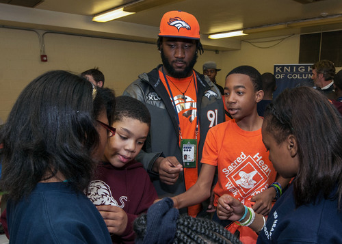 Defensive End Robert Ayers helps students pick out new coats on Jan. 28 at a Knights of Columbus Coats for Kids distribution at Sacred Heart School in Jersey City. Ayers attended this same school as a child.  (PRNewsFoto/Knights of Columbus)
