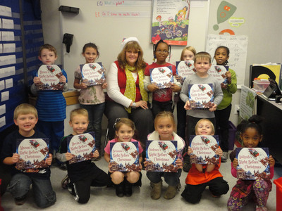 A classroom of first-graders at Anawalt Elementary School in Anawalt, West Virginia, along with educator Debbie Elmore, show off their new books. Chronicle Books, the publisher, and First Book, a national nonprofit, provided 10,000 brand-new books to kids in need, including the students at Anawalt Elementary.  (PRNewsFoto/First Book)
