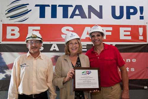 NC DOL Commissioner Cherie Berry presents the Safety and Health Achievement Recognition Program (SHARP) flag and plaque to (l.) Terminal Operator, James Branch, and (r.) Terminal Manager Dave Kreitinger for ongoing, effective workplace safety and health management systems. Titan America's Castle Hayne Terminal has not had a lost time accident in nearly 15 years.  (PRNewsFoto/Roanoke Cement Company)