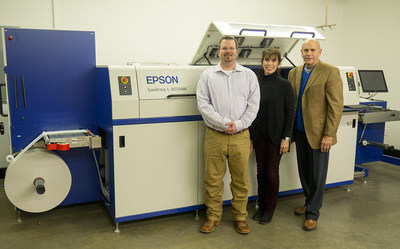 The Ranger Label team, from the left, are Daniel Deweese, Carol Anger, and Bob Anger, standing next to the SurePress L-4033AW