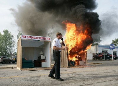 Illinois fire official Mike Figolah narrates a fire and sprinkler burn demonstration.