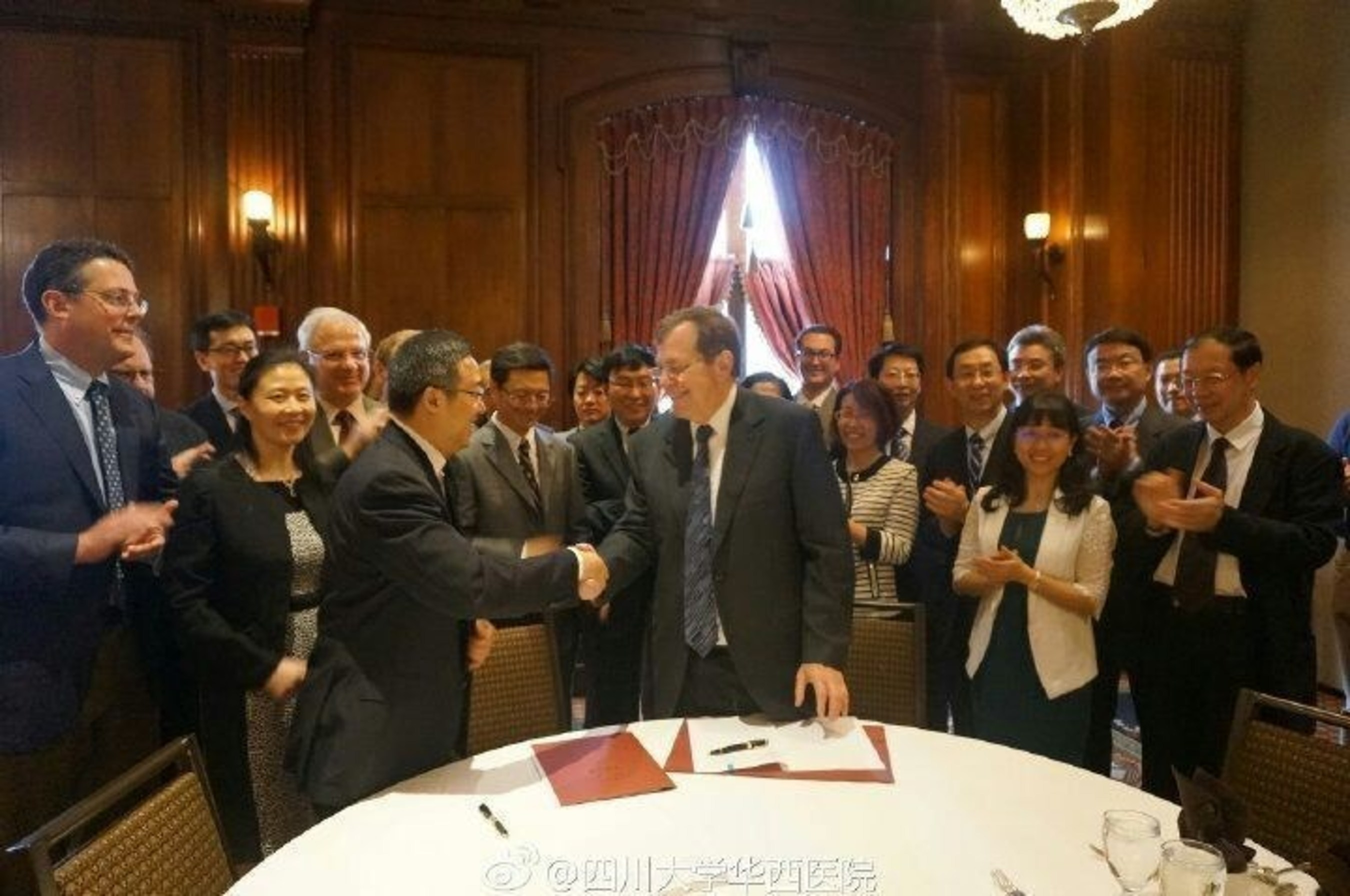 The director of West China Hospital, Sichuan University Prof. Li Weimin shakes hands with the representative of  ...