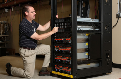 IBM test engineer Scott Reichmann inspects one of IBM's new enterprise Power Systems at the company's Rochester, MN, manufacturing site. The result of more than $1.4 billion in R&D investment by IBM, the systems are part of the company's continued focus on Smarter Computing systems aimed at solving the varied and intensifying challenges organizations are facing, from security vulnerabilities to managing ballooning data volumes that are expanding through social and mobile technologies.  (PRNewsFoto/IBM)