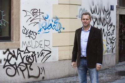 Flow East CEO, James Woolf stands in front of vandalised building in Old Town Prague. (PRNewsFoto/Flow East)
