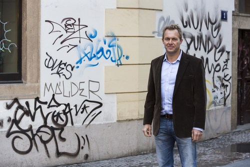 Flow East CEO, James Woolf stands in front of vandalised building in Old Town Prague. (PRNewsFoto/Flow East) ...