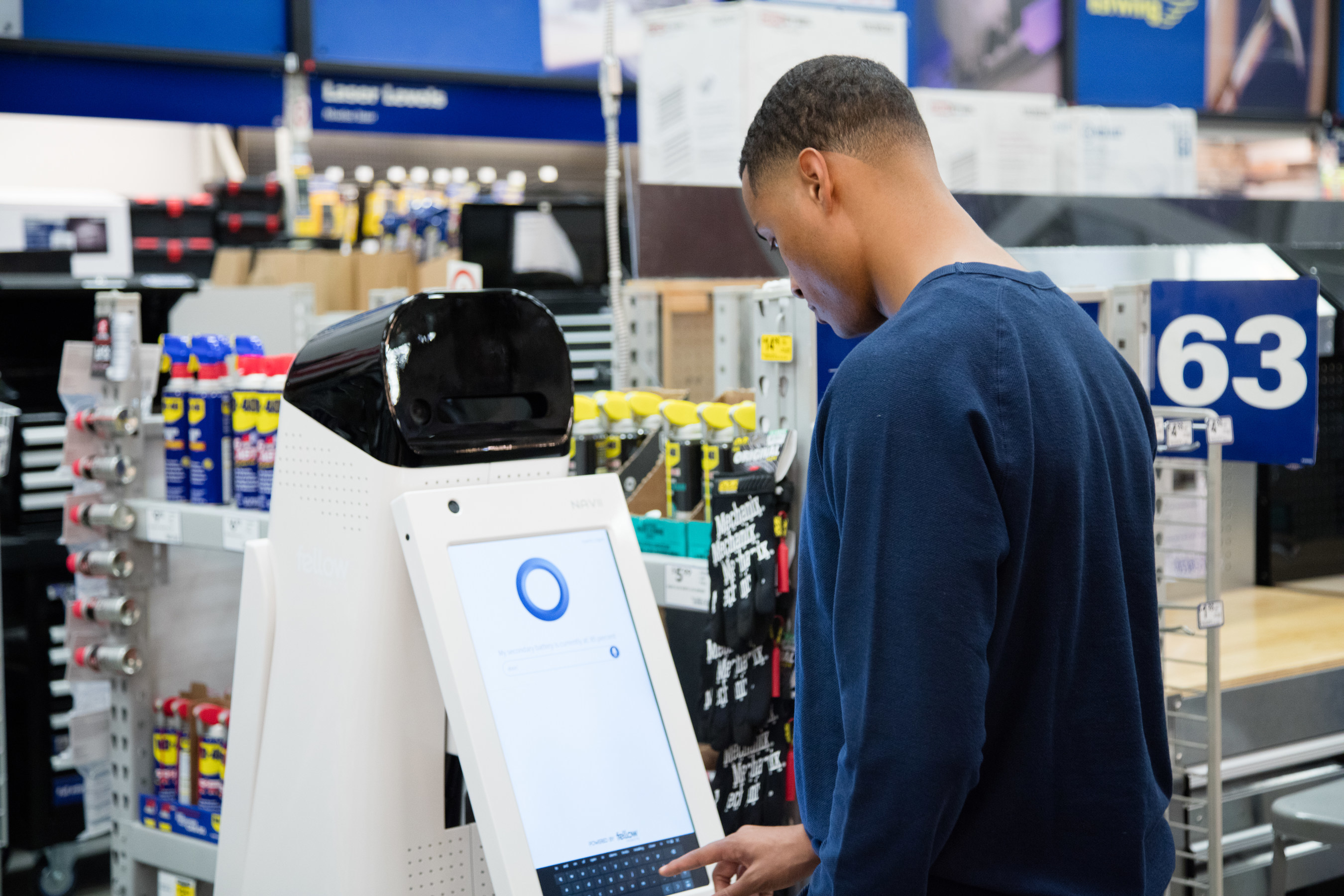 LoweBot helps a customer pull up product information.