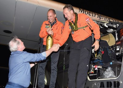 Jim Clerkin, President and CEO of Moet Hennessy North America, presents pilots Bertrand Piccard and Andre Borschberg with a golden jeroboam of Moet & Chandon celebrating the NYC arrival. Copyright: Getty Images (PRNewsFoto/Moet Hennessy)