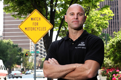 "Watch for Motorcycles: Allstate agent and motorcycle rider Jeff Lincoln stands in front of the first ""Watch for Motorcycles"" sign installed in the U.S."