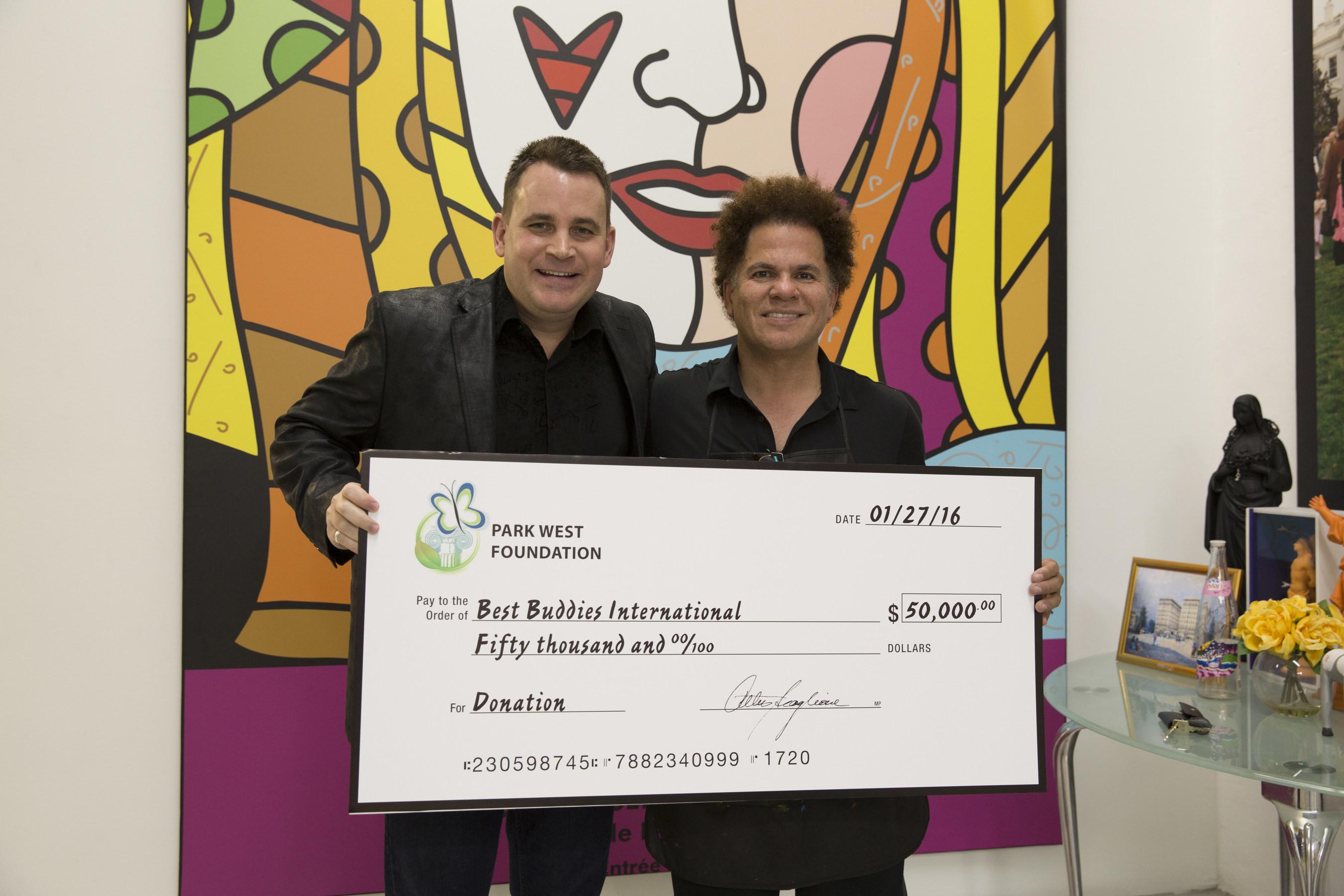 Park West Gallery VIP Art Director Jason Betteridge presents a $50,000 check to Romero Britto that will benefit Best Buddies International. (Credit: Park West Gallery)
