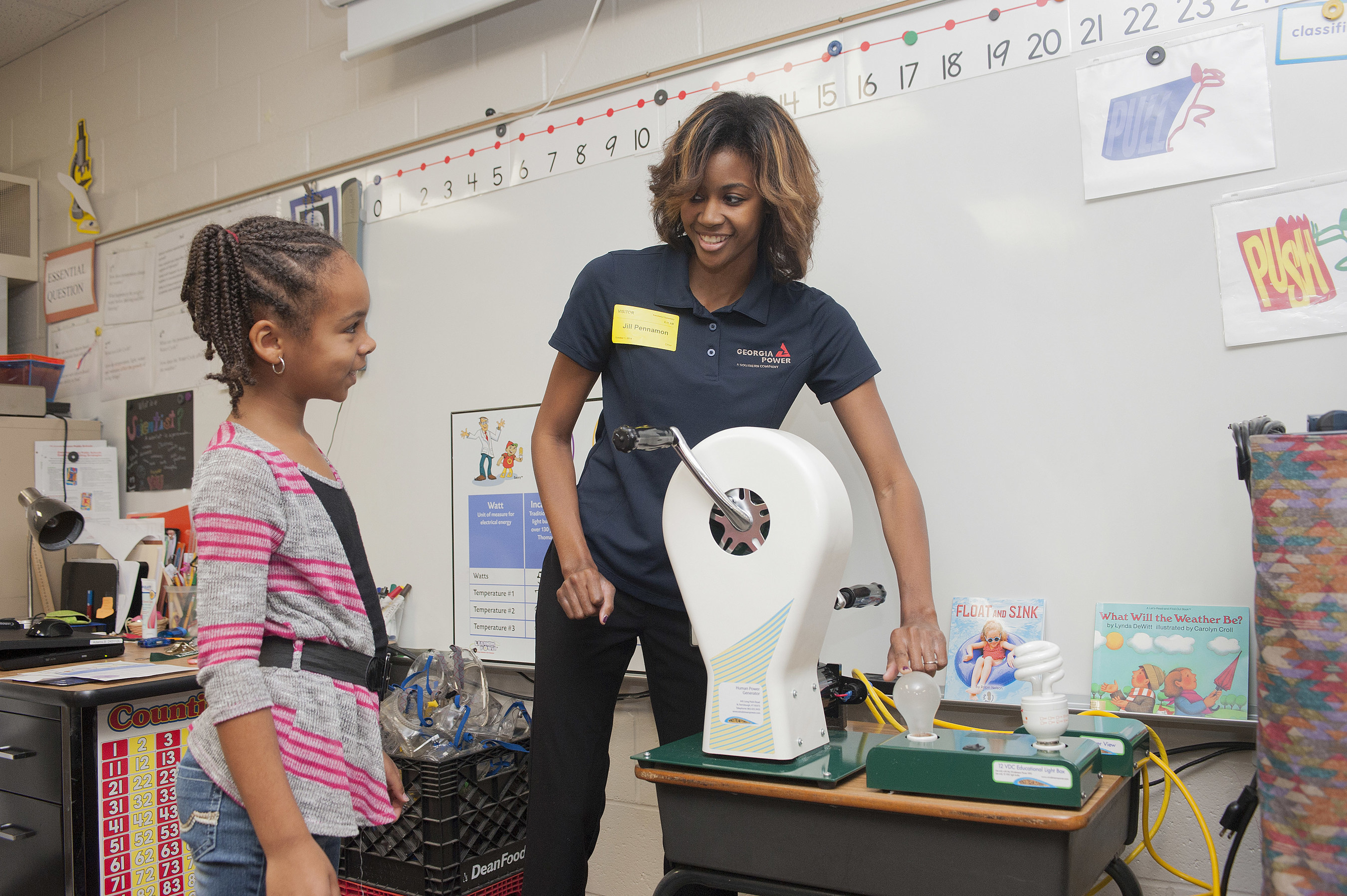A Georgia Power Learning Power coordinator demonstrates how much less energy a CFL bulb uses than a traditional incandescent bulb for a student. Georgia Power hosted 3,200+ in-school events during the 2015-2016 school year.