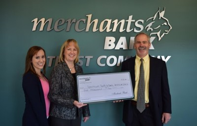 L-R Jessica Sturgeon, Marketing Coordinator and Cheryl Houchens, CRA and Compliance Officer from Merchants Bank present check to Mark Redmond of Spectrum.