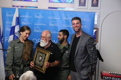 "Col. (res.) ""Katcha"" Cahaner who fought to reunify Jerusalem in the Six day war holds the ""Guardian of Zion"" award at the Jerusalem day celebration in the FOZ Museum honored by Israeli soldiers and Michael Evans Jr., FOZ Museum CEO"