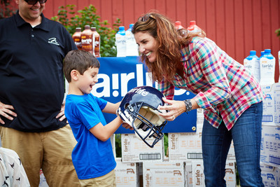 fairlife(R) co-founder, Sue McCloskey, gifts Brady Carpenter a football helmet, symbolic of fairlife's gift of a lifetime supply of ultra-filtered milk so that Brady can achieve his quarterback dreams.