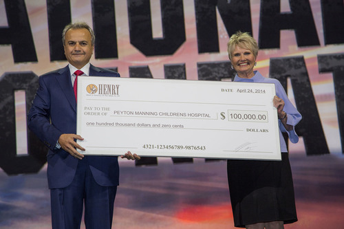 Anthony Imperato, president of Henry Repeating Arms donates $100,000 to Sue Anne Gilroy, Executive Director of the Peyton Manning Children's Hospital. (PRNewsFoto/Henry Repeating Arms)