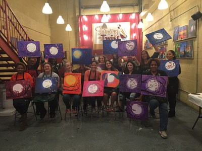 Ladies Night Painting attendees proudly display their vibrant, individual takes on the theme: Moonlight Cherry Blossoms.