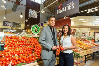 Gerardo Reyes Chavez of CIW and Felis Andrade of Giant Food place a Fair Food sign next to tomatoes in Giant's O Street store in Washington DC.  Photo credit: Helena Coutinho