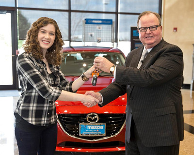 Mazda North American Operations President and CEO, Jim O'Sullivan, presents the keys to an all-new 2014 Mazda3 to Lauren Carter, who purchased the 10-millionth Mazda sold in the US at Continental Mazda in Naperville, Ill. on October 21, 2013.  (PRNewsFoto/Mazda North American Operations)