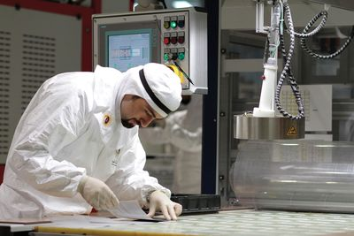 A Qatar Solar Energy technician examines a component of a solar panel
