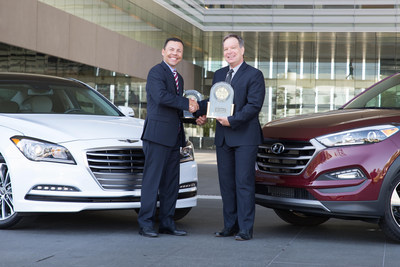Mircea Gradu, director, engineering & quality, Hyundai Motor America accepts 2016 U.S. Tech Experience Index trophies for the Hyundai Tucson and Hyundai Genesis from Mike Battaglia, vice president, Automotive Retail Global Automotive Practice, J.D. Power.