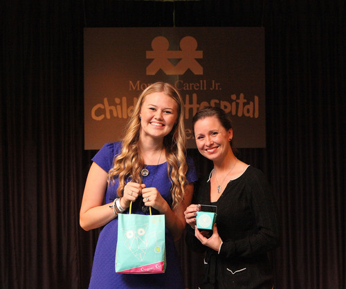 Origami Owl founder Bella Weems presents Kara Adams, Chair of Vanderbilt Children's Hospital Family ...