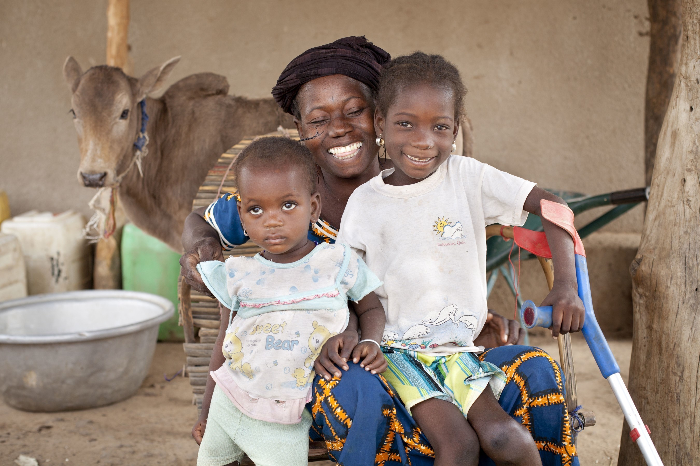 """Roukiatou (on the right-hand side) and her family. Every third child of primary school age without access to education has a disability; 150 million children worldwide live with a disability. Eighty percent of them live in developing countries and 9 out of 10 never have the chance to get an education. In order to break the cycle of poverty, the disability and development organization LIGHT FOR THE WORLD supports global efforts to ensure education for every child. Visit us at: www.light-for-the-world.org. picture credit :  """"Ulrich Eigner"""""""