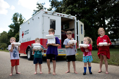 Children hold hot meals they received from the Red Cross in Denham Springs, a town hit hard by flooding across southern Louisiana. Red Cross photo by Marko Kokic