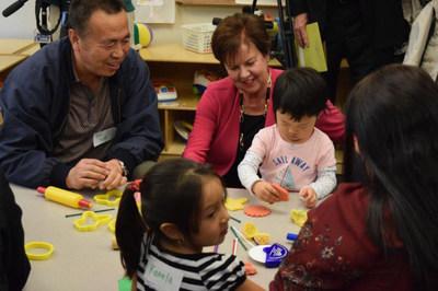 """""""Sharon Darling, presidenta y CEO de National Center for Families Learning, trabaja con Jasmine He y su abuelo, Yun Tong, en una reciente presentacion de Toyota Family Learning en Louisville, Kentucky""""."""