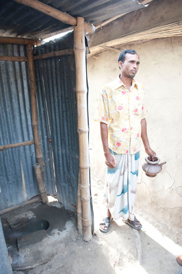 "Next to a typical Bangladesh latrine, a villager holds a ""bodna"" which holds about one liter of water and is poured down the latrine after use. The pit is directly under the latrine, allowing flies to easily enter and exit the pit, spreading disease. American Standard Brands, in partnership with the Bill & Melinda Gates Foundation, hopes to develop and test a low-cost, prefabricated toilet system that can correct this unsanitary practice.  (PRNewsFoto/American Standard Brands)"
