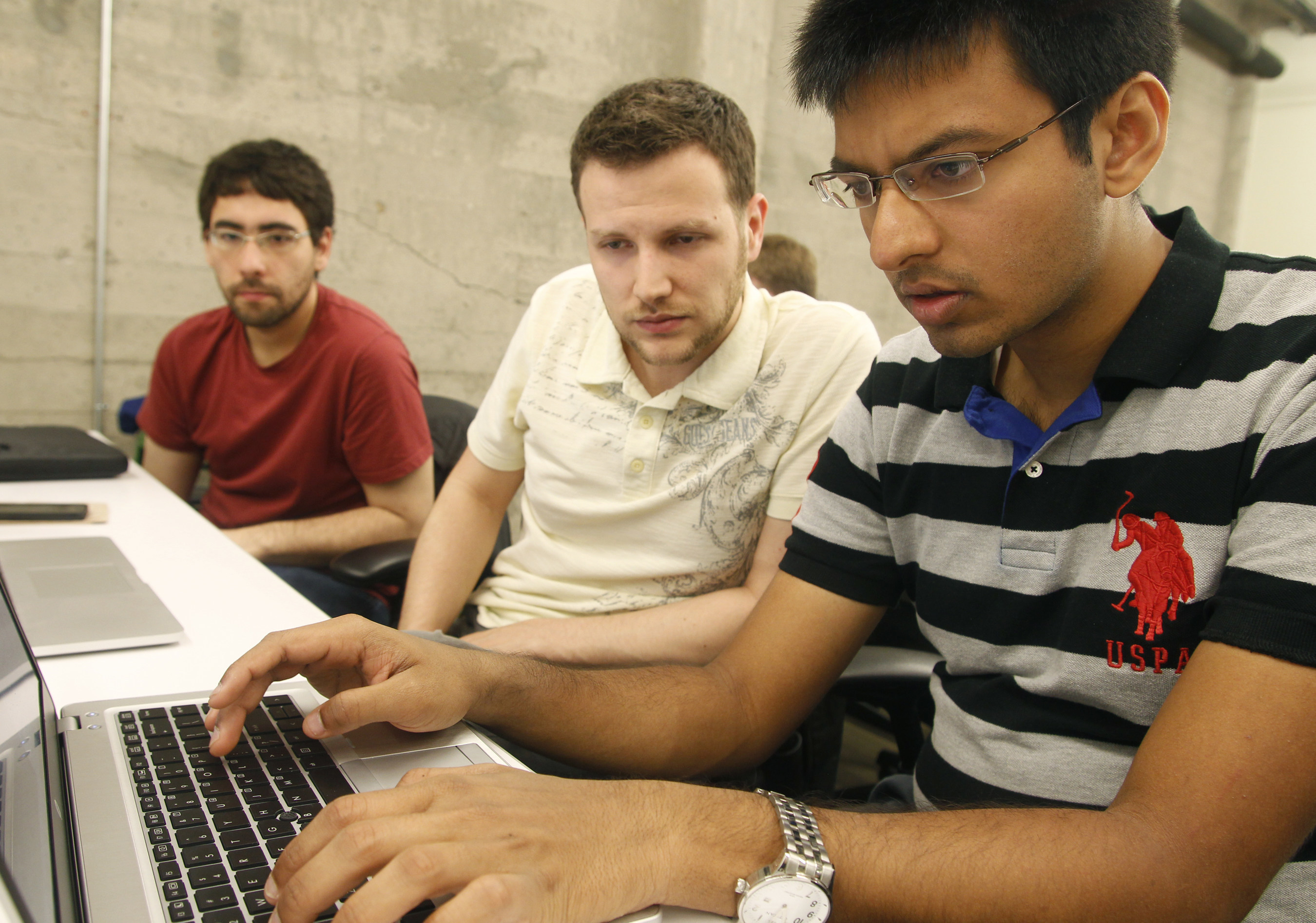 Shiva Gopalan, an engineering student at Texas A&M University, confers with IBM developers Henrique Copelli Zambon and Luiz Aoqui, during an IBM hosted Spark Hackathon at Galvanize, a tech hub in San Francisco.