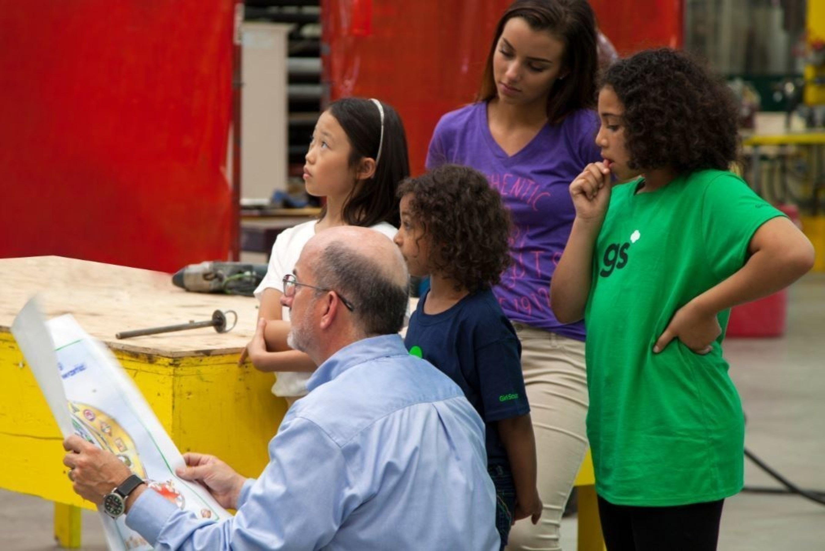 "Girls examine the Girl Scout-themed float sketch alongside John Piper, Vice President of Macy's Parade Studio, and analyze unique aspects of the float that showcase how Girl Scouts are ""building a better world."""
