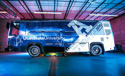 Utah State University has demonstrated a first-of-its-kind electric bus that is charged through wireless charging technology. The Aggie Bus, shown here in USU's Advanced Charging Bay, achieved several significant milestones.  It is the first bus developed and designed by a North American organization that is charged with wireless power transfer technology and is the world's first electric bus with WPT technology combining the three following performance metrics:  A power level up to 25 kilowatts, greater than 90 percent efficiency from the power grid to the battery and a maximum misalignment of up to six inches.  (PRNewsFoto/Utah State University)
