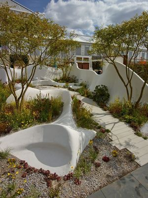 The Pure Land Foundation garden: A curvilinear white shimmering structure that captures the organic shapes of the landscapes and is inspired by nature's natural rhythms. The planting colour palette is influenced by the principal colours used in Buddhist art and ritual, warm yellows, oranges, blues and reds, which emerge through a matrix of tussocky grasses.  /  Image by Allan Pollok -Morris