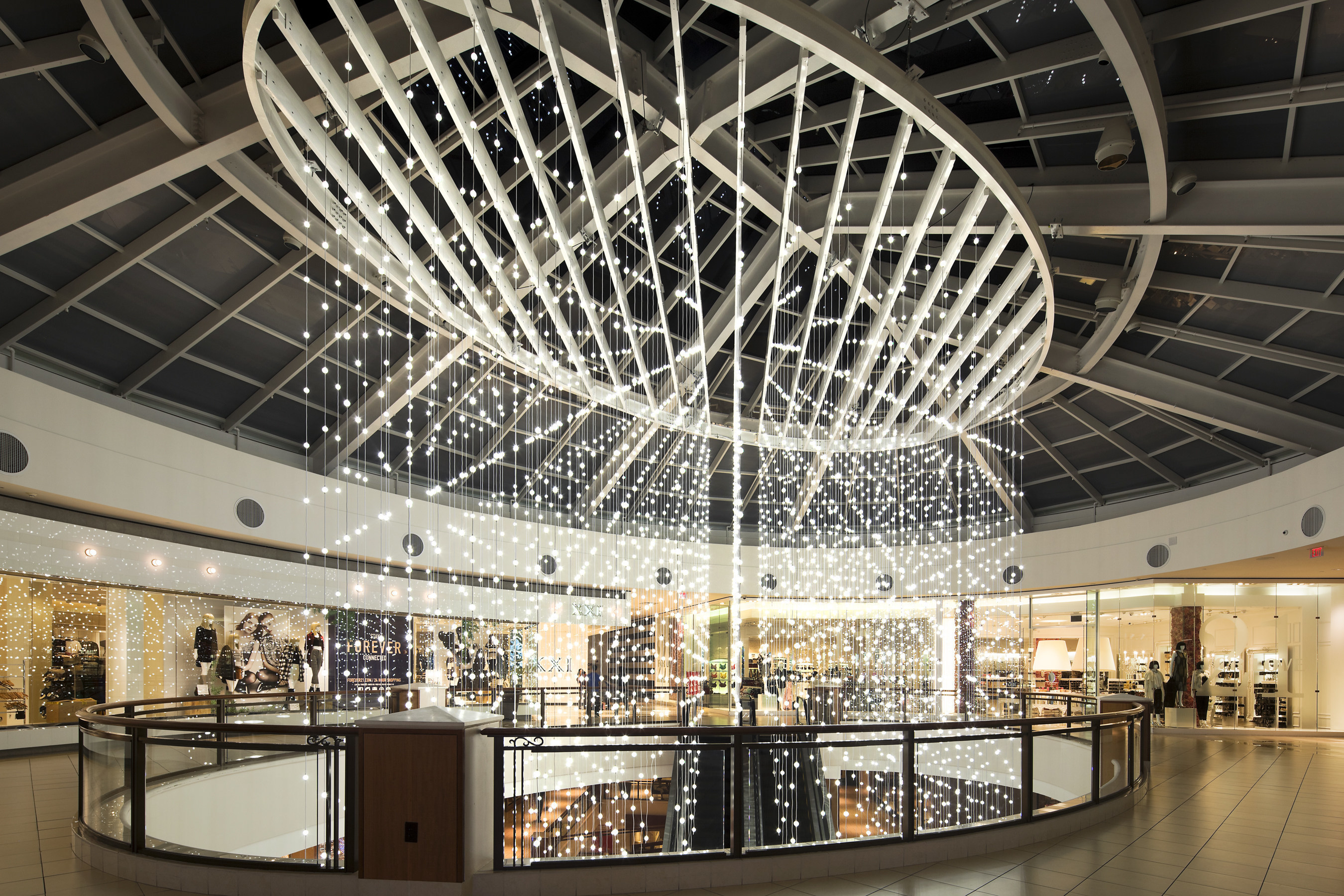 Aventura Mall's Twinkling Snowfall LED Installation, created by Snarkitecture, invites shoppers to experience the sensation of being swept into the middle of a wintery snowfall that appears to be floating down through the skylight of the three-story atrium.