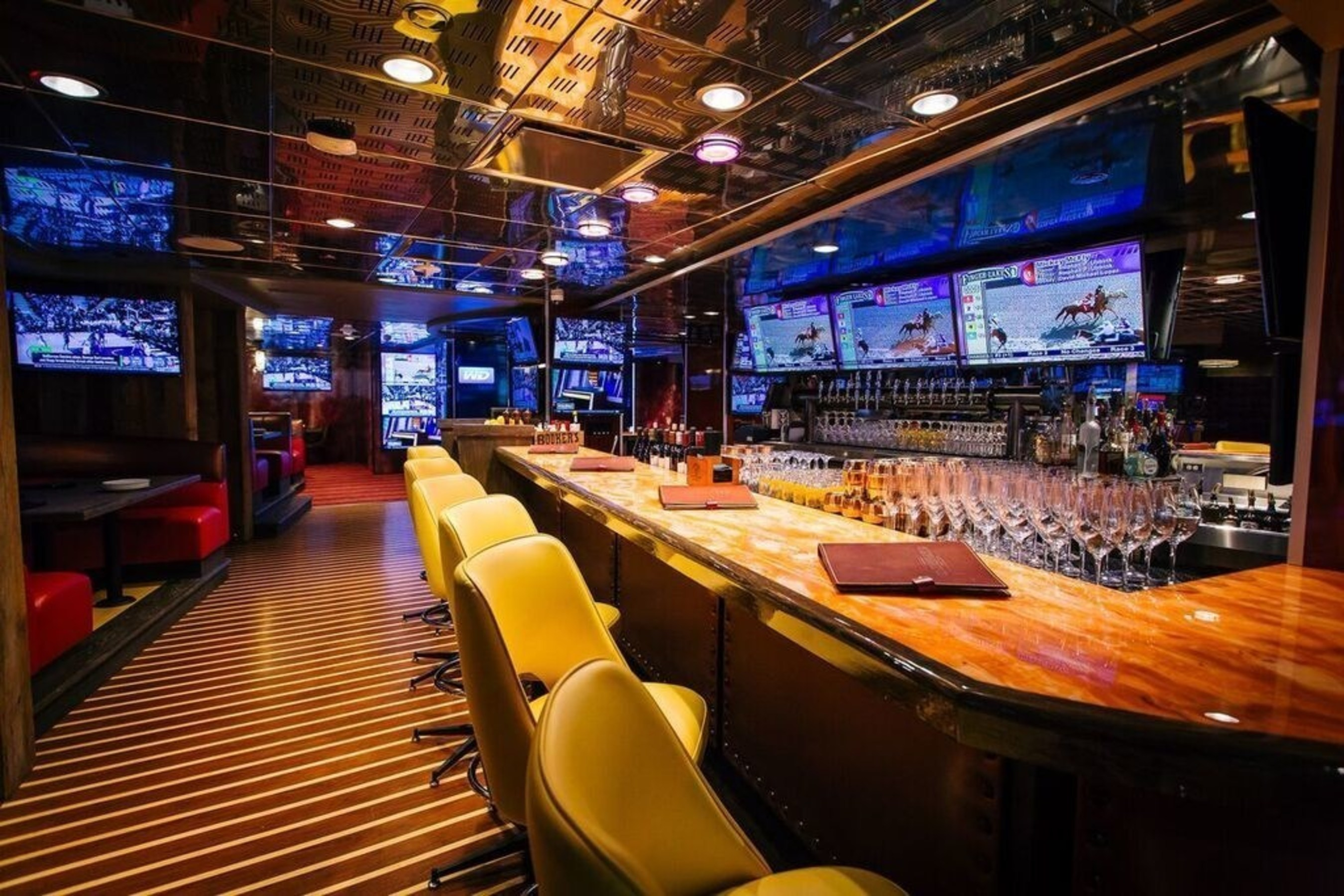 """Striders """"Turf Clublounge"""" where guests can relax, dine, and wager on horse racing in premium booth seating."""