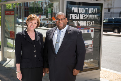"Nancy Fletcher, President & CEO, Outdoor Advertising Association of America, with Administrator David Strickland, National Highway Traffic Safety Administration, near a ""Stop the Texts. Stop the Wrecks."" bus shelter PSA in Washington, DC.  (PRNewsFoto/Outdoor Advertising Association of America)"