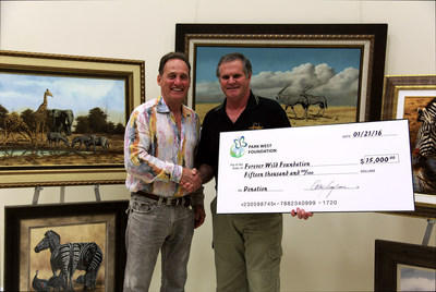 Park West Gallery Founder and CEO Albert Scaglione presents Andrew Bone with a $15,000 check to benefit the Forever Wild Foundation. (Credit: Park West Gallery)